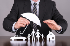man in a suit holding a paper umbrella over paper cut outs of a family beside a home and car